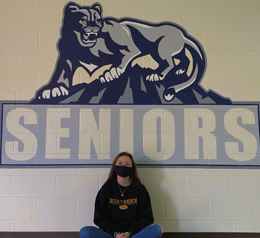 Alexis Kuykendoll sitting in front of the senior wall.
