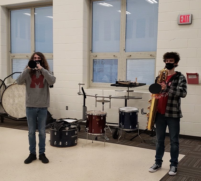 Senior Juston Quincy and sophomore Caden Murray warming up before a pep band basketball game, following the social distancing protocols.