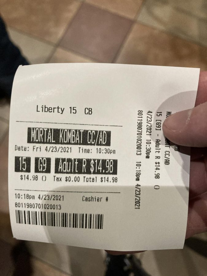 Samuel George stands in line for the movie with his ticket stub in hand.