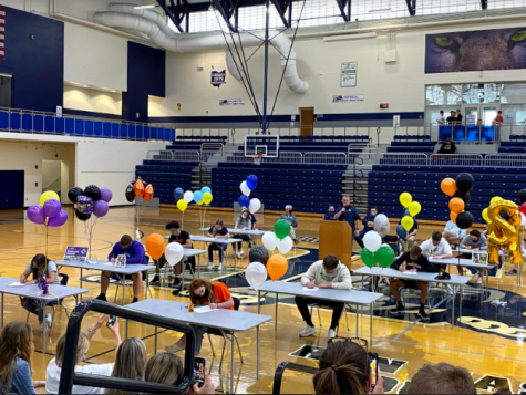 The senior athletes sign at the college signing ceremony.